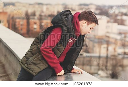 teenager looks at the city sitting on the edge of the roof house