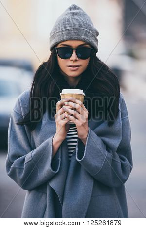 Autumn snuggles. Beautiful young woman holding coffee cup and looking at camera while standing outdoors