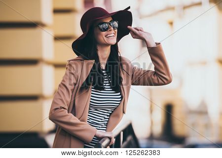 Looking at the sky with smile. Beautiful young woman adjusting her hat and looking away with smile while leaning to fence outdoors
