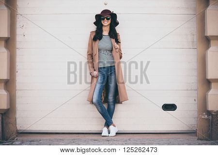 Stylish and cheerful. Full length of beautiful young woman  looking at camera with smile while standing outdoors
