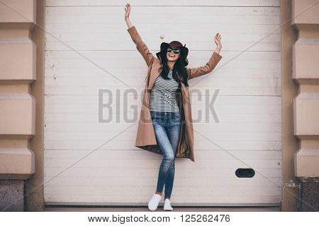 Feeling carefree. Full length of beautiful young woman  looking away with smile and keeping arms outstretched while standing outdoors
