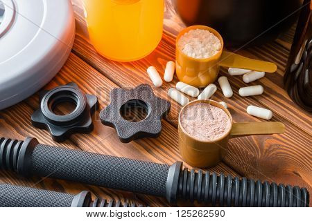 Dumbbell With Plastic Stamp, And Sports Nutrition Shaker On Wooden Background
