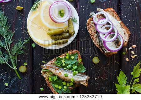Fish Sandwiches And A Plate With Lemon Onions And Gherkins