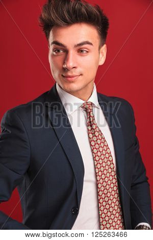 closeup portrait of attractive young businessman in black suit with red tie, with open jacket, posing in red studio background while looking away from the camera