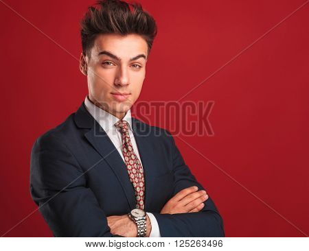 closeup portrait of attractive young businessman in black suit with red tie, posing in red studio background with hands crossed while looking at the camera