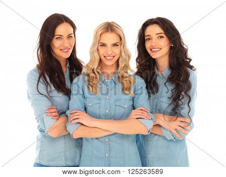 three confident casual women standing with hands crossed on white studio background