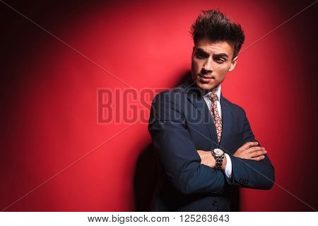 portrait of confident young businessman in black suit with red tie posing with hands crossed while frowning and looking away from the camera in red studio background