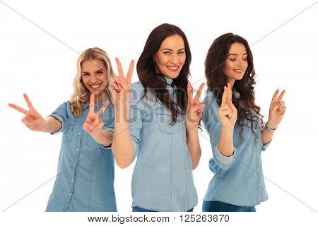 3 young casual women laughing and making victory sign on white studio background