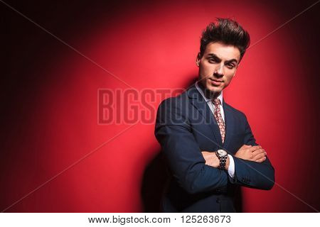 portrait of confident young businessman in black suit with red tie posing with hands crossed while frowning and looking at the camera in red studio background