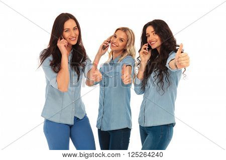 3 casual women talking on the phone making the ok thumbs up hand sign on white studio backogrund