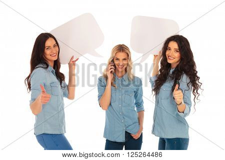 young women making the ok thumbs up hand sign and holding speech bubbles while their firend is talking on the phone on white background
