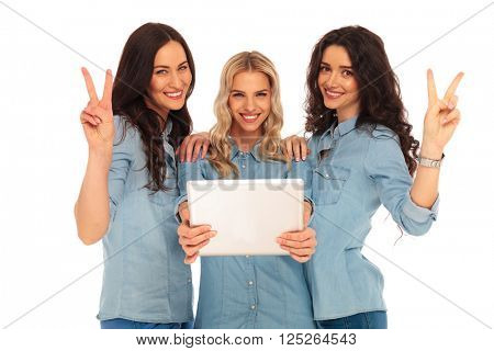 three casual women with a tablet pad computer, making vicotry hand sign on white background