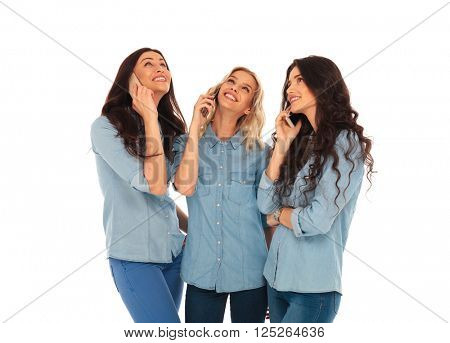 3 casual woman talking on the phone and looking up to something on white studio background