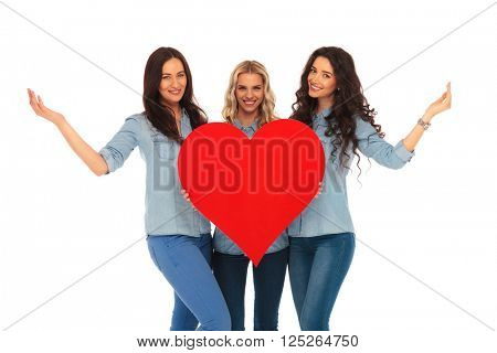 three smiling casual women welcoming to their heart, on white studio background