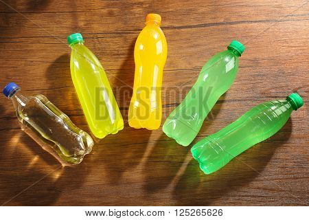 Soda bottles on the wooden table, top view
