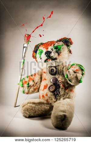 Artist teddy bear holding the paintbrush like a magic staff