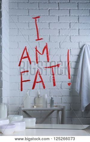 Text I AM FAT written on mirror in the bathroom