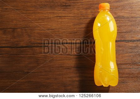 Soda bottle on the wooden table, top view