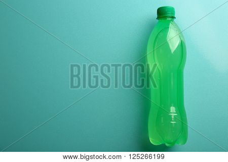 Bottle of soft drink on the blue background, top view