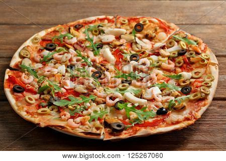 Pizza with seafood, red pepper and olives on wooden table