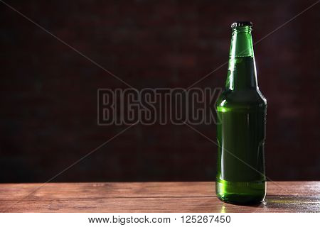 Green glass bottle of beer on dark background, close up