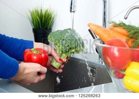 woman washing broccoli and pepper with water in kitchen