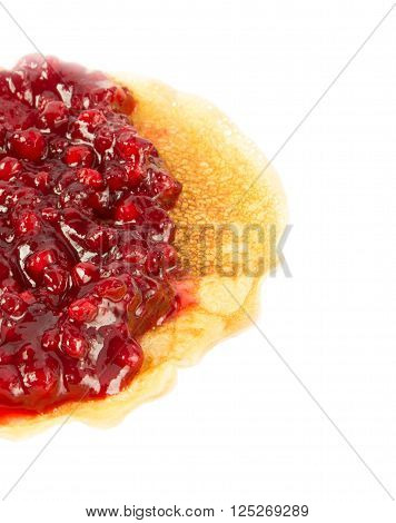 Pancake half with cowberry jam on a white background