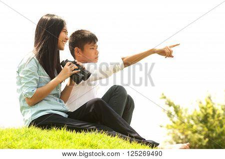 Asian young boy and girl sit on mound seeking Binoculars.