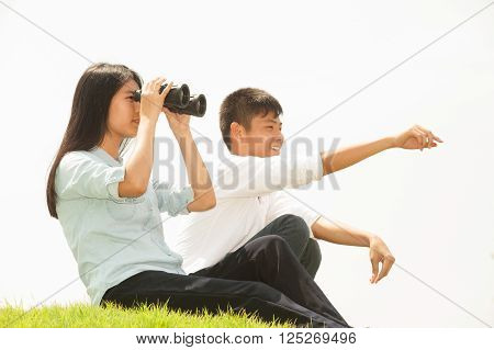 Asian young boy and girl sit on mound seeking Binoculars. ** Note: Soft Focus at 100%, best at smaller sizes