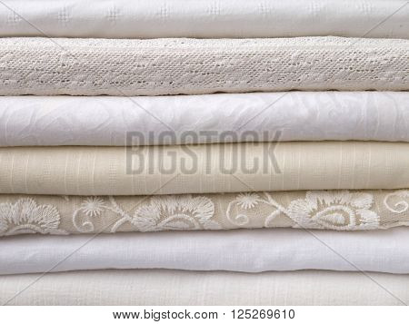 Stack of cool summer white and ivory clothes with different textures