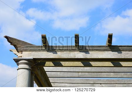 Edge of wooden pergola with sky in background