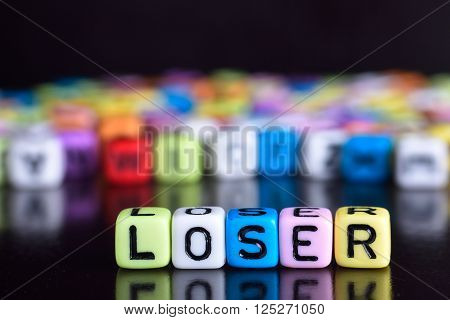 Colorful cube with word loser on wooden table