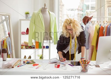 Fashion designer working in sketch at her creative office
