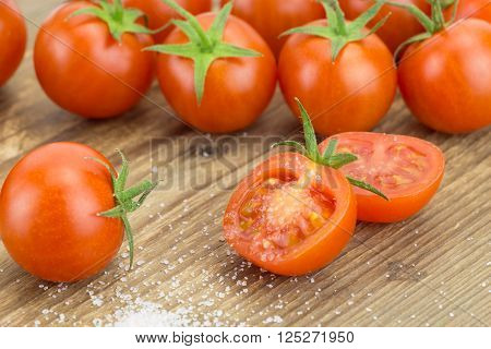Heap Of Cherry Tomatoes With One Cut In Half And Pinch Of Salt, On Wooden Surface.