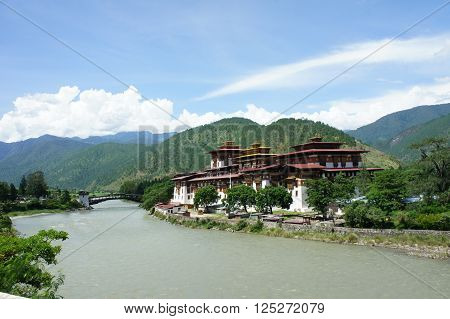 Punakha Dzong in Bhutan located at the confluence of 2 major rivers which are the Pho Chhu and Mo Chhu. Blue sky and mountains set as a background.