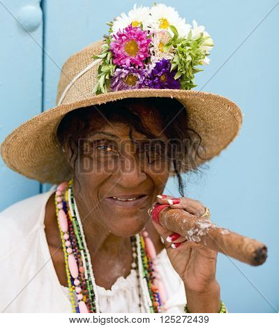 HAVANA - CUBA / 05.03.2015: Elderly woman is smoking in the street of Havana Vieja