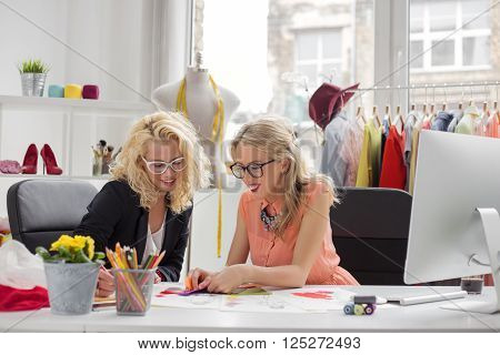 Two creative fashion designers looking at sketch