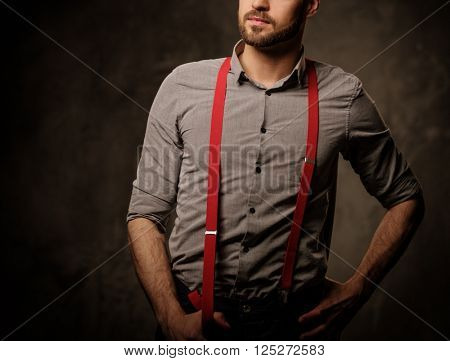 Young handsome man with beard wearing suspenders and posing on dark background.