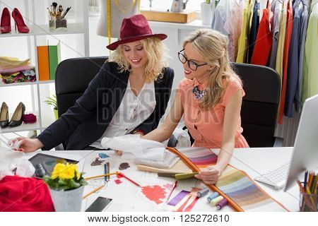 Two fashion designers looking at sketch at their studio