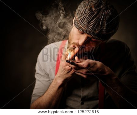 Serious old-fashioned man in tweed hat lighting a cigar on dark background.