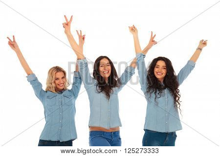 three excited young casual women with hands in the air celebrating victory on white astudio background