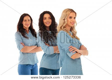 side view of three confident casual women standing with hands crossed on white background and looking away from the camera