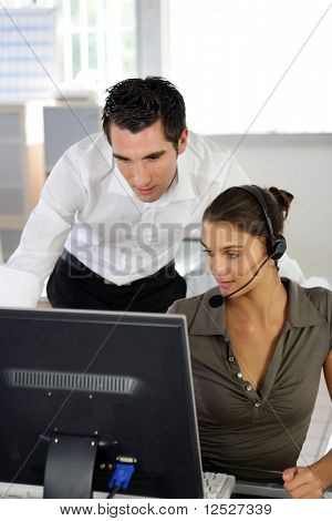 A man and a woman in an office in front of a computer