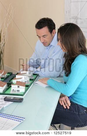 Couple watching an architect model in an office