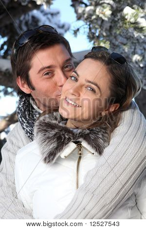 Portrait of a smiling man kissing a woman on the cheek