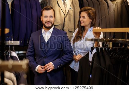 Confident handsome man with beard choosing a jacket in a suit shop.