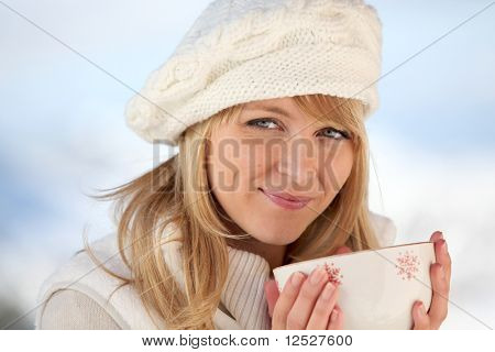 Portrait of a smiling woman with a wool hat holding a cup
