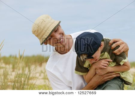 Man tickling a little boy