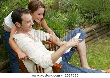 Smiling man and woman reading a book in the garden