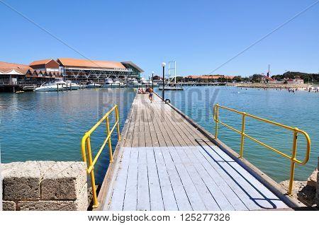 HILLARYS,WA,AUSTRALIA-JANUARY 22,2016: Jetty with tourists, marina and swimming cove at Hillarys Boat Harbour in Hillarys, Western Australia.